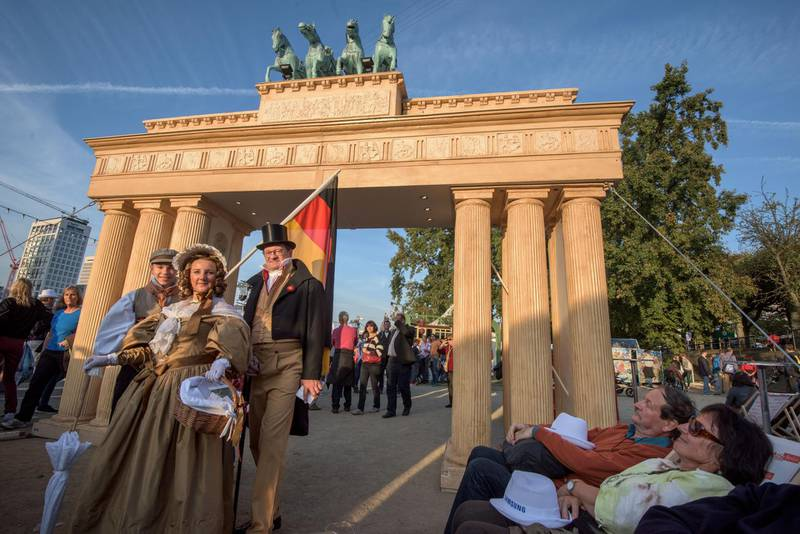 FRANKFURT AM MAIN, GERMANY - OCTOBER 03:  Elen Suchoroschenko (C), Fabio Begnotti (L) and Stefan Suchoroschenko (R) dressed in traditinell clothes of the 'Biedermeier' period of 1832 promote the 'Hambacher Castle' in front of a mock of the 'Brandenburger Tor' at the 25th anniversary citizens festival of German reunification on October 3, 2015 in Frankfurt, Germany. On October 3, 1990, following the end of the Cold War, western-oriented, capitalist and democratic West Germany and post-revolution, formerly communist East Germany reunited into a single state after 41 years of official separation. Though the integration of the two former states into one is seen by most as a success, differences remain, particularly in average incomes and pensions, which in eastern Germany are lower.  (Photo by Thomas Lohnes/Getty Images)