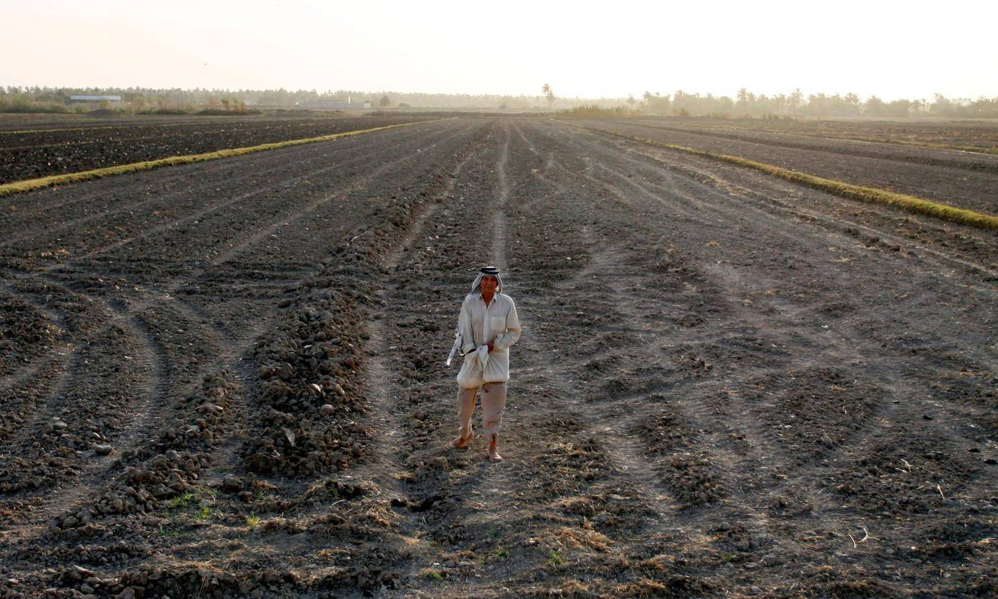 An Iraqi man stands on a dry field in an area affected by drought in the Mishkhab region, central Iraq, some twenty-five kilometres from Najaf, on July 2, 2018. Facing an unusually harsh drought, the agriculture ministry last month suspended the cultivation of rice, corn and other cereals, which need large quantities of water. The decision has slashed the income of amber rice farmers, who usually earn between 300,000 and 500,000 dinars ($240 to $400) a year per dunum (quarter-acre, 0.1 hectares) of land. / AFP / Haidar HAMDANI
