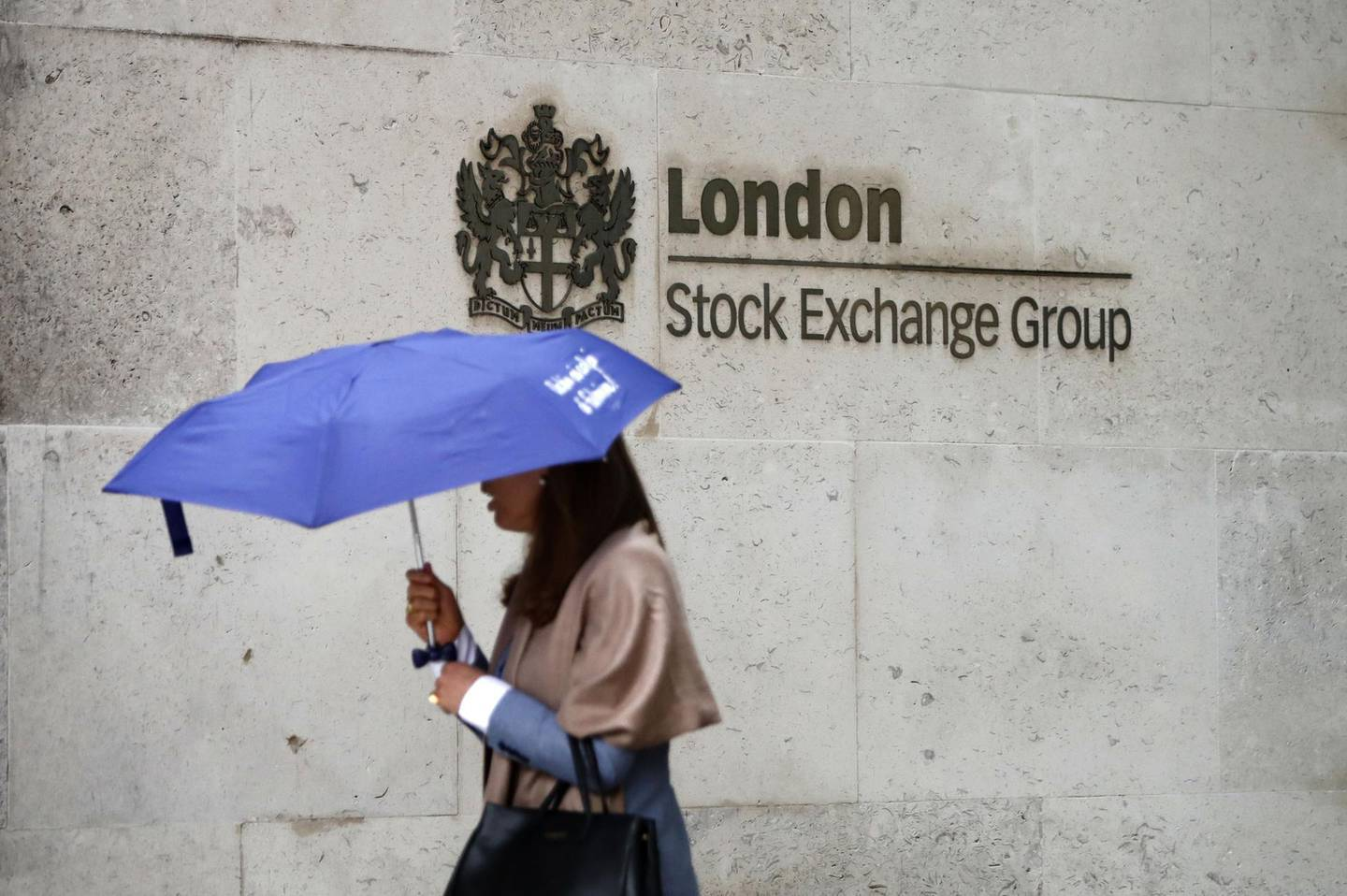 (FILES) This file photo taken on August 09, 2017 shows a commuter walking past the London Stock Exchange in the City of London on August 9, 2017.  London Stock Exchange Group shareholders are to vote on whether to hasten chairman Donald Brydon's exit following investor anger at the departure of chief executive Xavier Rolet, the LSEG announced December 1, 2017. / AFP PHOTO / Tolga AKMEN
