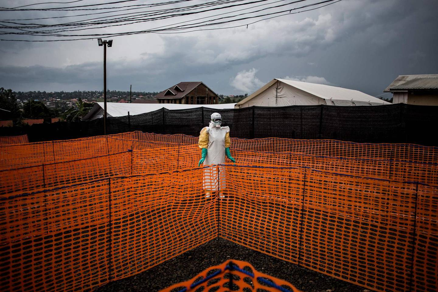 """(FILES) In this file photo taken on November 07, 2018 A health worker waits to handle a new unconfirmed Ebola patient at a newly build MSF (Doctors Without Borders) supported Ebola treatment centre (ETC) on November 7, 2018 in Bunia, Democratic Republic of the Congo. A woman died of the Ebola virus disease in eastern Democratic Republic of Congo on February 7, 2021, Congolese Health Minister Eteni Longondo announced, noting the """"resurgence"""" of the disease in the country. / AFP / John WESSELS"""