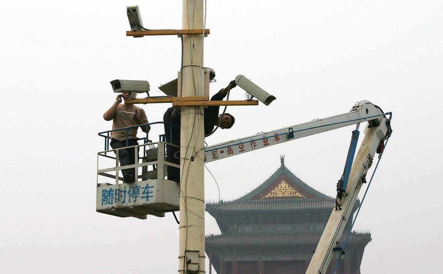 BEIJING - SEPTEMBER 28: Labourers adjust newly installed surveillance cameras at Tiananmen Square ahead of National Day on September 28, 2005 in Beijing, China. The capital city has tightened security as China prepares for its celebrations of the 56th anniversary of the founding of People's Republic of China on October 1.  (Photo by Guang Niu/Getty Images)
