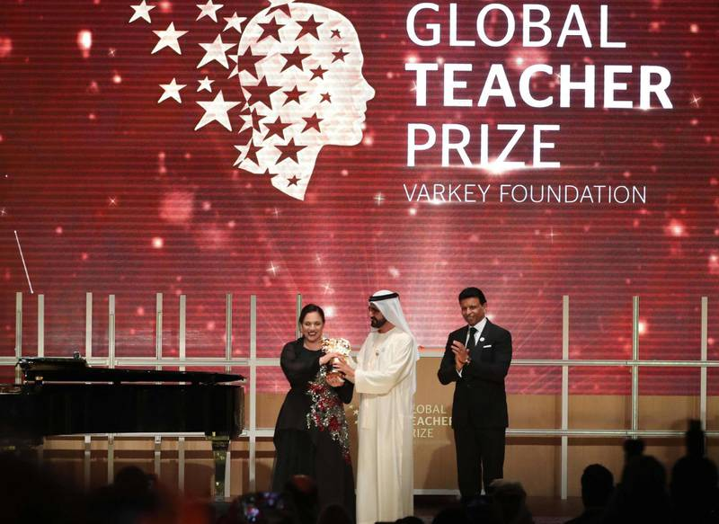 """British teacher Andria Zafirakou (L) receives the """"Global Teacher Prize"""" from Sheikh Mohammed bin Rashid al-Maktoum (C), Vice-President and Prime Minister of the UAE and Ruler of Dubai during an award ceremony in Dubai on March 18, 2018. Zafirakou who  was among ten finalists chosen from 179 countries, won one million dollars of prize money. / AFP PHOTO / KARIM SAHIB"""