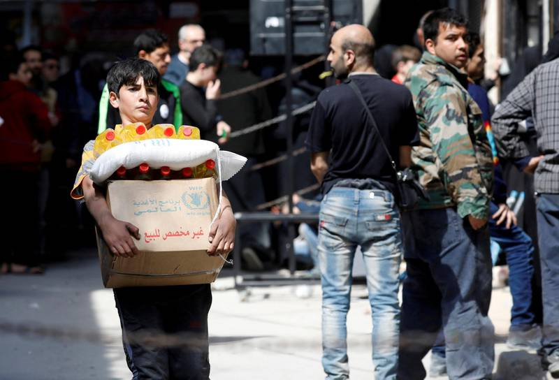 FILE PHOTO: A boy holds a cardboard box of food aid received from World Food Programme in Aleppo's Kalasa district, Syria April 10, 2019. Picture taken April 10, 2019. REUTERS/Omar Sanadiki/File Photo