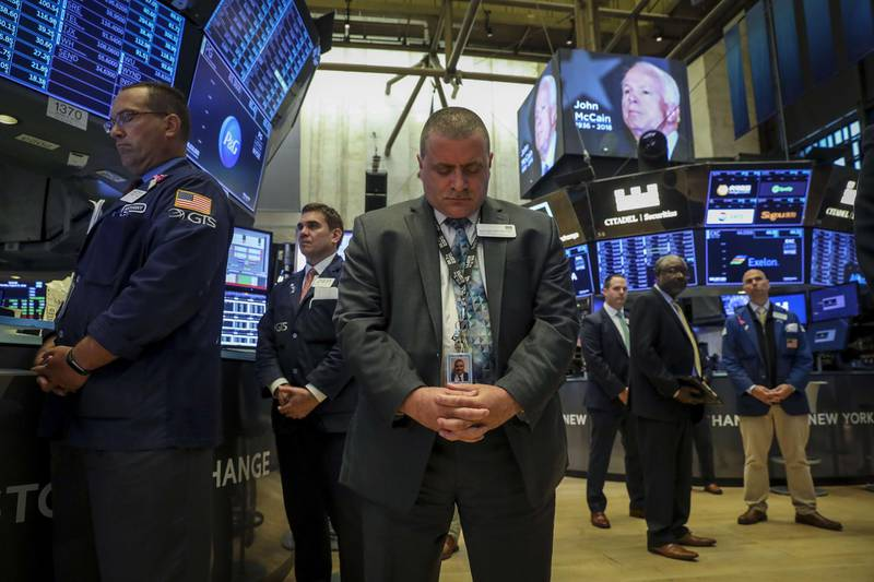 NEW YORK, NY - AUGUST 27: Traders and financial professionals observe a moment of silence for the late U.S. Senator John McCain prior to the opening bell on the floor of the New York Stock Exchange (NYSE), August 27, 2018 in New York City. McCain passed away on August 25 following a long battle with brain cancer.   Drew Angerer/Getty Images/AFP == FOR NEWSPAPERS, INTERNET, TELCOS & TELEVISION USE ONLY ==