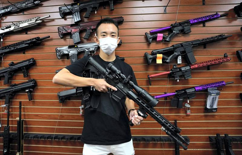 Tom Cai shows off a long gun at Jimmy's Sport Shop in Mineola, New York on September 25, 2020. - Gun store owners on Long Island have been selling out of firearms as scores of customers fear a rise in violence as the pandemic escalates in the area. (Photo by TIMOTHY A. CLARY / AFP)