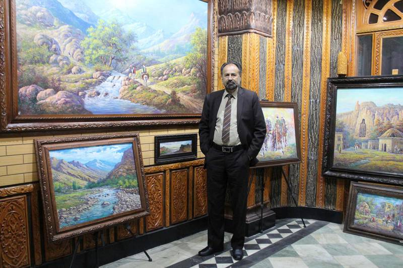Dr. Mohammad Yousef Asefi by his paintings on the second floor of his gallery. His work often showcases Afghanistan's landscapes and Afghan's way of life , past and present. The picture was taken prior to the power cut that was suspected to have been caused by the Taliban. Photo by Sarvy Geranpayeh