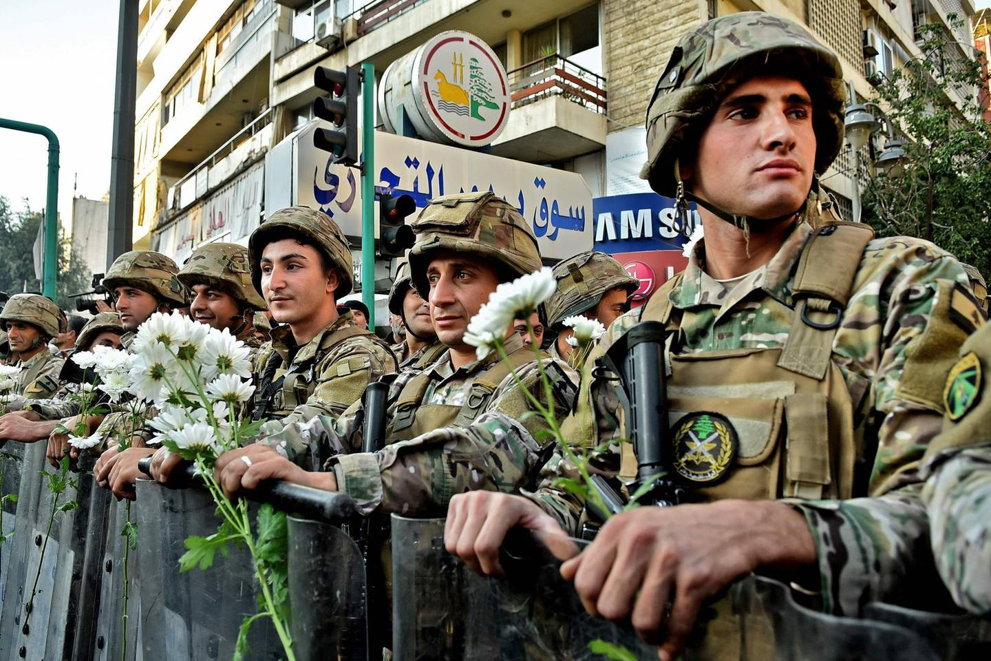 Lebanese army soldiers carry flowers offered to them by a supporter of outgoing Lebanese premier Saad Hariri during a protest in Beirut's Corniche al-Mazraa neighbourhood on December 20, 2019. Anger was fuelled among members of Lebanon's Sunni community who said the prime-minister-designate did not enjoy the sect's backing for a post reserved for Sunni Muslims by a power-sharing system enshrined after the end of the 1975-1990 civil war. / AFP / -
