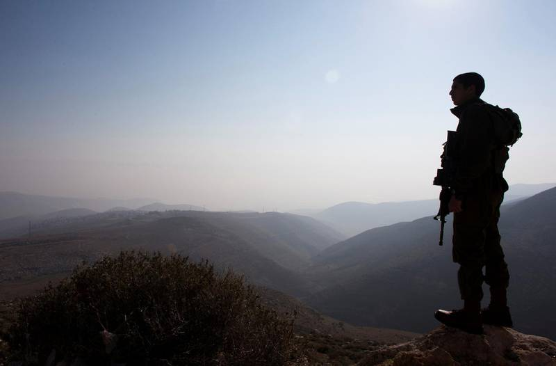 FILE PHOTO: File photo- An Israeli soldier stands guard during a tour made by Israeli parliament members in the Jordan Valley near the Jewish settlement of Maale Efrayim January 2, 2014.      REUTERS/Ronen Zvulun/File Photo