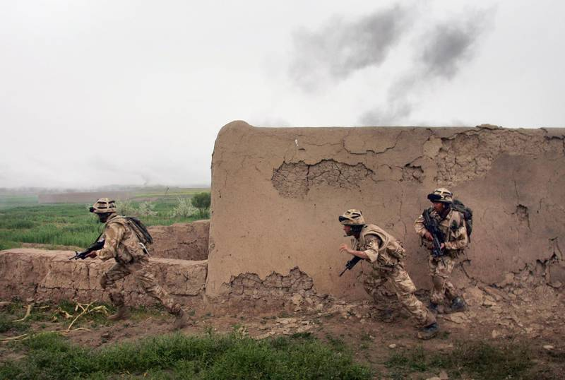 KAJAKI, AFGHANISTAN - MARCH 18:  British Marines run under fire from Taliban during a morning operation on March 18, 2007 near Kajaki in the Afghan province of Helmand. Members of the 42 Royal Marines attacked a Taliban held village on the outskirts of Kajaki in a morning operation to push Taliban insurgents further back from a British camp at the Kajaki Dam. Operation Achilles involves some 4,500 NATO troops and is meant to secure more area near the US-Built dam so it can be upgraded and its electrical output expanded.  (Photo by John Moore/Getty Images)