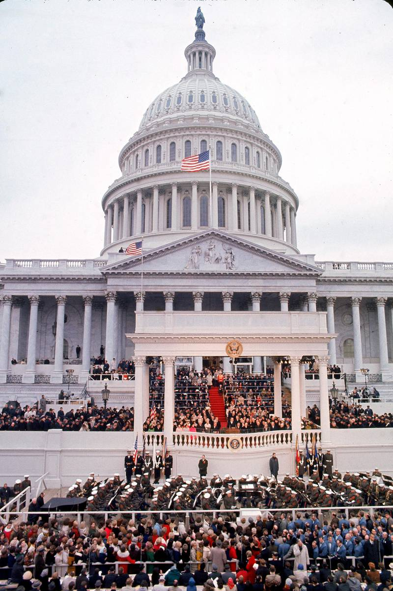 Overhead view of the crowd as they watch American President Richard Nixon (1913 - 1994) deliver his inaugural address at a podium in front of the Capitol Building, Washington DC, January 20, 1969. First Lady Pat Nixon (1912 - 1993) is visible in the front row to the President's right, dressed in a red coat. (Photo by Charles H. Phillips/The LIFE Picture Collection via Getty Images)