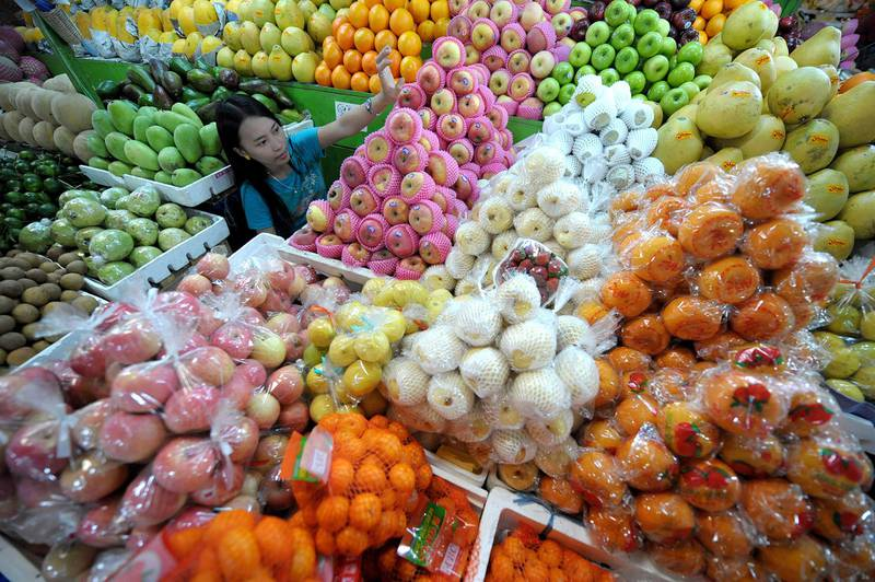 A vendor arranges round-shaped fruit at a market in suburban Manila on December 27, 2010.  Some Filipinos believe that displaying 12 different round-shaped fruits - one representing each month of the year - at home before New Year's Day welcomes prosperity.   AFP PHOTO/NOEL CELIS (Photo by NOEL CELIS / AFP)