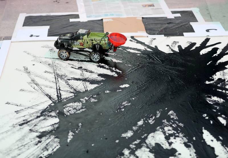 Dubai, United Arab Emirates - October 20, 2019: Artist Sharan Anil creates art using a remote control car at the One year to go celebrations. Sunday the 20th of October 2019. Burj Park, Dubai. Chris Whiteoak / The National