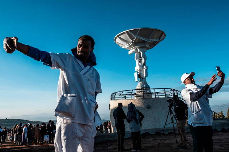 People take selfie pictures in front of a satellite antenna during the ceremony for the launching of the Ethiopian Remote Sensing Satellite (ETRSS) in Entoto Observatory and Research Centre in Addis Ababa, on December 20, 2019. Ethiopia launched its first satellite on December 20, 2019, a landmark achievement for the country's space programme that caps a banner year for the African space industry. The launch of the Ethiopian Remote Sensing Satellite (ETRSS) took place at a space station in China, though scores of Ethiopian and Chinese officials and scientists gathered at the Entoto Observatory and Research Centre outside the capital, Addis Ababa, early Friday to watch a live broadcast / AFP / EDUARDO SOTERAS