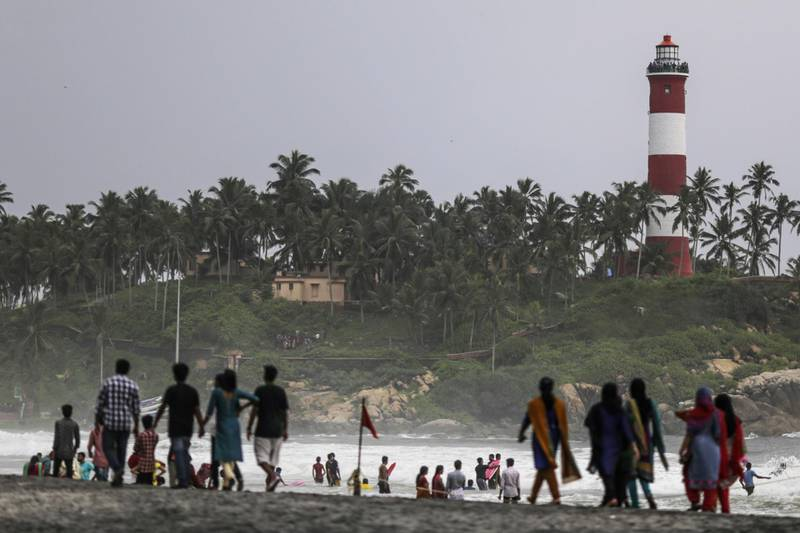Visitors walk along Lighthouse Beach in Kovalam, Kerala, India, on Sunday, May 31, 2015. Prime Minister Narendra Modi is counting on a revival in credit to accelerate growth in Asia's third-largest economy after the RBI cut its benchmark interest rate three times this year. Photographer: Dhiraj Singh/Bloomberg