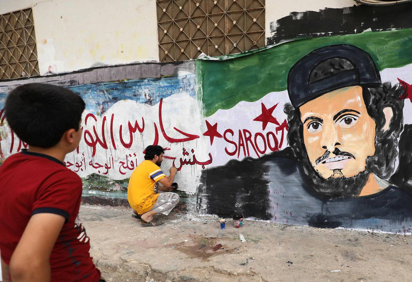 TOPSHOT - A child watches as a local artist works on a mural painting showing the late Syrian rebel fighter Abdel-Basset al-Sarout in the town of Binnish in the jihadist-held northern Idlib province on June 8, 2019. The Syrian goalkeeper turner rebel fighter who starred in an award-winning documentary died of his wounds today aged 27 after fighting regime forces in northwest Syria, a monitor and his faction said. Al-Sarout was a goalkeeper from the central city of Homs, who became its most popular singer of protest songs after Syrian uprising broke out in March 2011.  / AFP / OMAR HAJ KADOUR