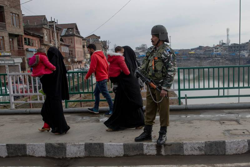 Kashmiri women carry children and walk past an Indian Paramilitary soldier standing guard on a bridge in central Srinagar, Indian controlled Kashmir, Thursday, Feb. 20, 2020. Thursday marks 200 days since India stripped Kashmir of its semi-autonomy and statehood and imposed a total communications blackout. Indian authorities are easing internet access but continue a ban on popular social media platforms such as Facebook, WhatsApp and Twitter. Top Kashmiri leaders also continue to be under arrest. (AP Photo/ Dar Yasin)