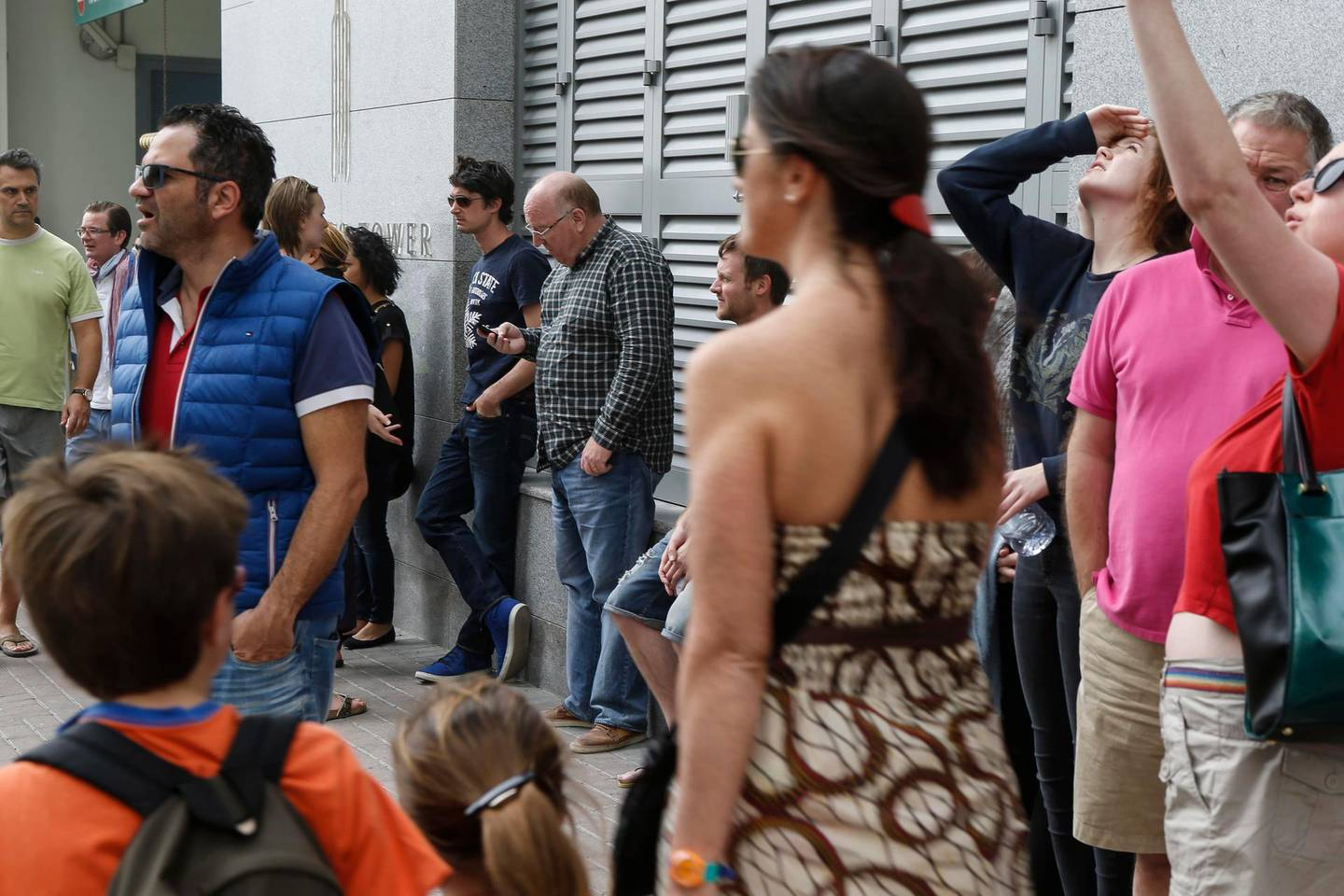 DUBAI, UNITED ARAB EMIRATES, 21 FEBRUARY, 2015. Residents of the Torch tower in the Dubai Marina gather in front of the building waiting to get the go ahead from Civil Defense and building managemanet to enter their respective apartments. (Photo: Antonie Robertson) Journalist: Dana Moukhallati. Section: National. *** Local Caption ***  AR_2102_Torch_After_Fire-10.JPG