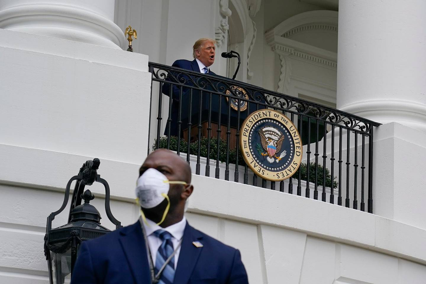 President Donald Trump speaks from the Blue Room Balcony of the White House to a crowd of supporters, Saturday, Oct. 10, 2020, in Washington. On the lower left is a member of the Secret Service wearing a face mask. (AP Photo/Alex Brandon)