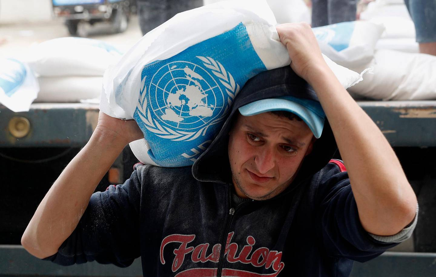 A Palestinian worker carries sacks of flour distributed by the United Nations Relief and Works Agency (UNRWA) for poor refugee families, at the Sheikh Redwan neighborhood of Gaza City, Tuesday, March 31, 2020. The United Nations has resumed food deliveries to thousands of impoverished families in the Gaza Strip after a three-week delay caused by fears of the coronavirus. UNRWA, provides staples like flour, rice, oil and canned foods to roughly half of Gaza's 2 million people. (AP Photo/Adel Hana)