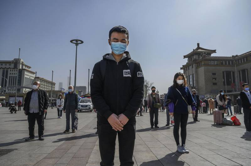 BEIJING, CHINA - APRIL 04: Chinese travellers wear protective masks as they bow their heads at 10 AM for three minutes of silence to mark the country's national day of mourning for COVID-19 at Beijing Railway Station on April 4, 2020 in Beijing, China. Across the country people paused, and sirens and horns wailed for three minutes to remember medical personnel and patients who died during the coronavirus outbreak. With the pandemic hitting hard across the world, officially the number of coronavirus cases in China is dwindling, since the government imposed sweeping measures to keep the disease from spreading.  For two months, millions of people across China have been restricted in how they move from their homes, while other cities have been locked down in ways that appeared severe at the time but are now being replicated in other countries trying to contain the virus. In Beijing, it is mandatory to wear masks outdoors, retail stores operate on reduced hours, restaurants employ social distancing among patrons, and tourist attractions at risk of drawing large crowds remain closed. Since January, China has recorded more than 81,000 cases of COVID-19 and at least 3200 deaths, mostly in and around the city of Wuhan, in central Hubei province, where the outbreak first started. (Photo by Kevin Frayer/Getty Images)