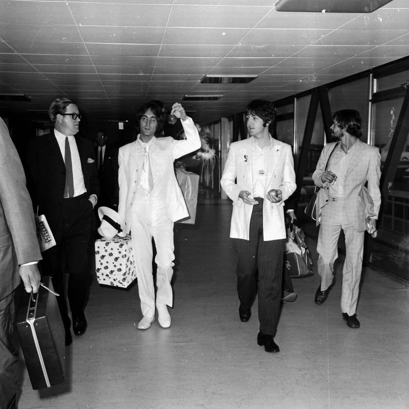 John Lennon and Paul McCartney, of The Beatles, arriving at London Airport, 16th May 1968. They are both dressed in white and carrying apples to promote their new company Apple Corps. (Photo by George Stroud/Express/Getty Images)