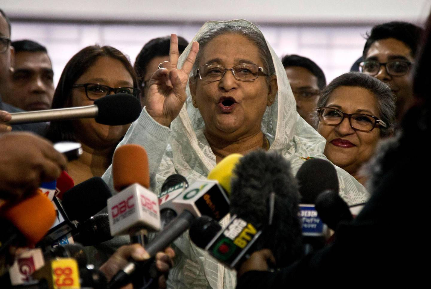 Bangladesh Prime Minister Sheikh Hasina flashes a victory sign as she speaks to the media persons after casting her vote in Dhaka, Bangladesh, Sunday, Dec. 30, 2018. Voting began Sunday in Bangladesh's contentious parliamentary elections, seen as a referendum on what critics call Prime Minister Sheikh Hasina's increasingly authoritarian rule. (AP Photo/Anupam Nath)