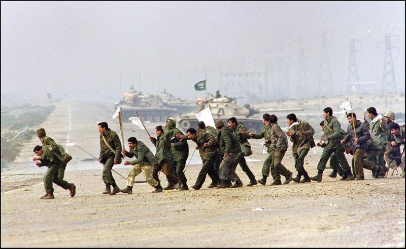 """TO GO WITH STORIES ON TWENTIETH ANNIVERSARY OF IRAQI INVASION OF KUWAIT (FILES) Iraqi soldiers cross a highway carrying white surrender flags 25 February 1991 in Kuwait City. Iraq's invasion of Kuwait 02 August 1990, ostensibly over violations of the Iraqi border, led to the Gulf War which began 16 January 1991. A U.S.-led multinational force expelled Iraq from Kuwait during the """"Desert Storm"""" offensive and a cease-fire was signed 28 February 1991. (Photo by CHRISTOPHE SIMON / AFP)"""