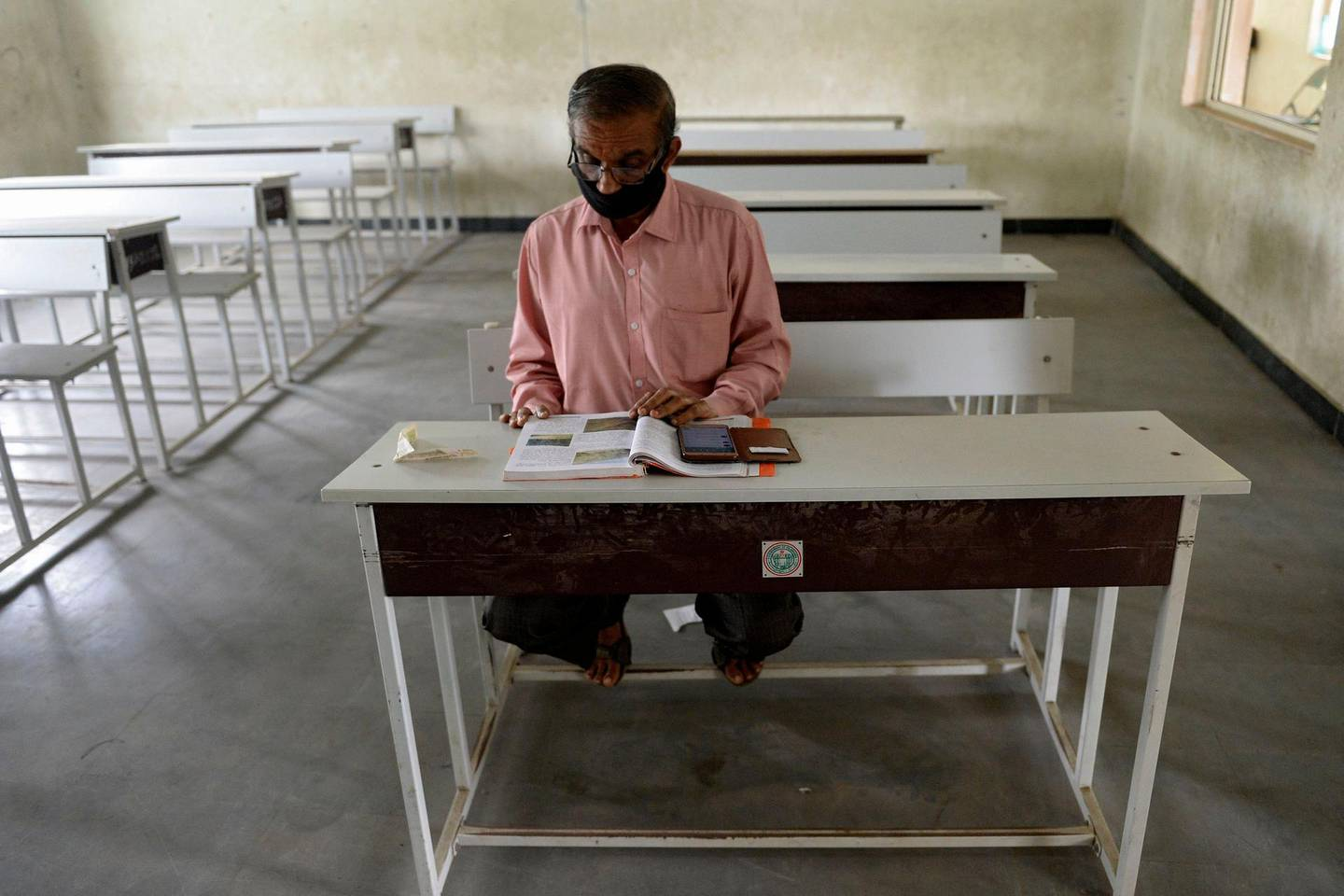 A teacher sits in an empty classroom as he prepares for online teaching at a government high school in Hyderabad on September 21, 2020, after the state government allowed 50 percent of staff at schools and colleges to resume duties for tele-counselling and online teaching amid Covid-19 coronavirus pandemic. / AFP / NOAH SEELAM