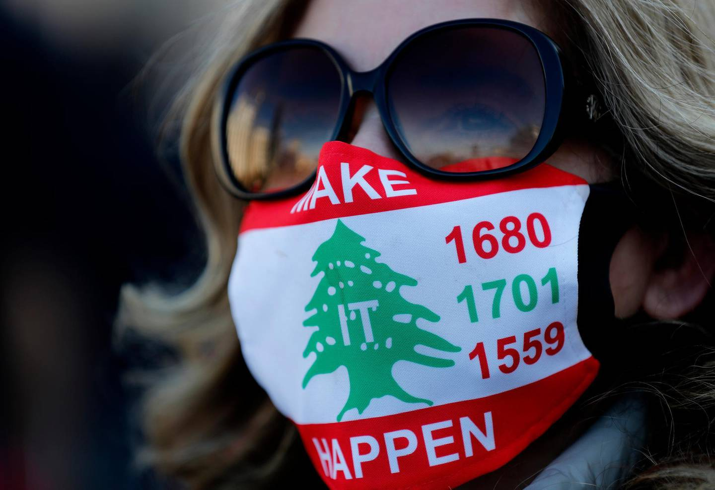 An activist wears a mask to protect from COVID-19, with the colors of the Lebanese flag and the U.N. Resolutions numbers that called for disarmament all Lebanese and non-Lebanese militias, during a sit-in to mark the 47th anniversary of the 1975-90 Civil War, in Beirut, Lebanon, Tuesday, April 13, 2021. The 15-year Civil War began on April 13, 1975 and killed more than 150,000 people. (AP Photo/Hussein Malla)