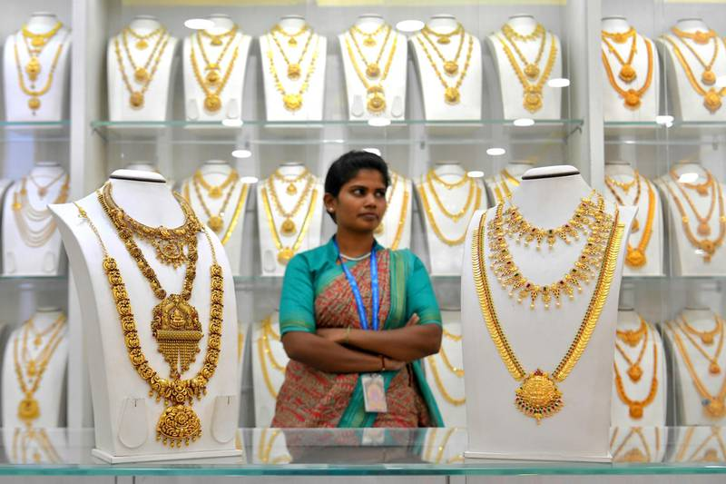 A saleswoman stands next to gold necklaces at a jewellery store in Bangalore on July 5, 2019.  India's newly re-elected government promised on July 5 an easing of foreign investment rules and more infrastructure spending in an effort to boost flagging growth rates and create jobs. India has been leap-frogged by China as the world's fastest-growing major economy, with unemployment in Asia's third-biggest economy at its highest since the 1970s.  / AFP / MANJUNATH KIRAN