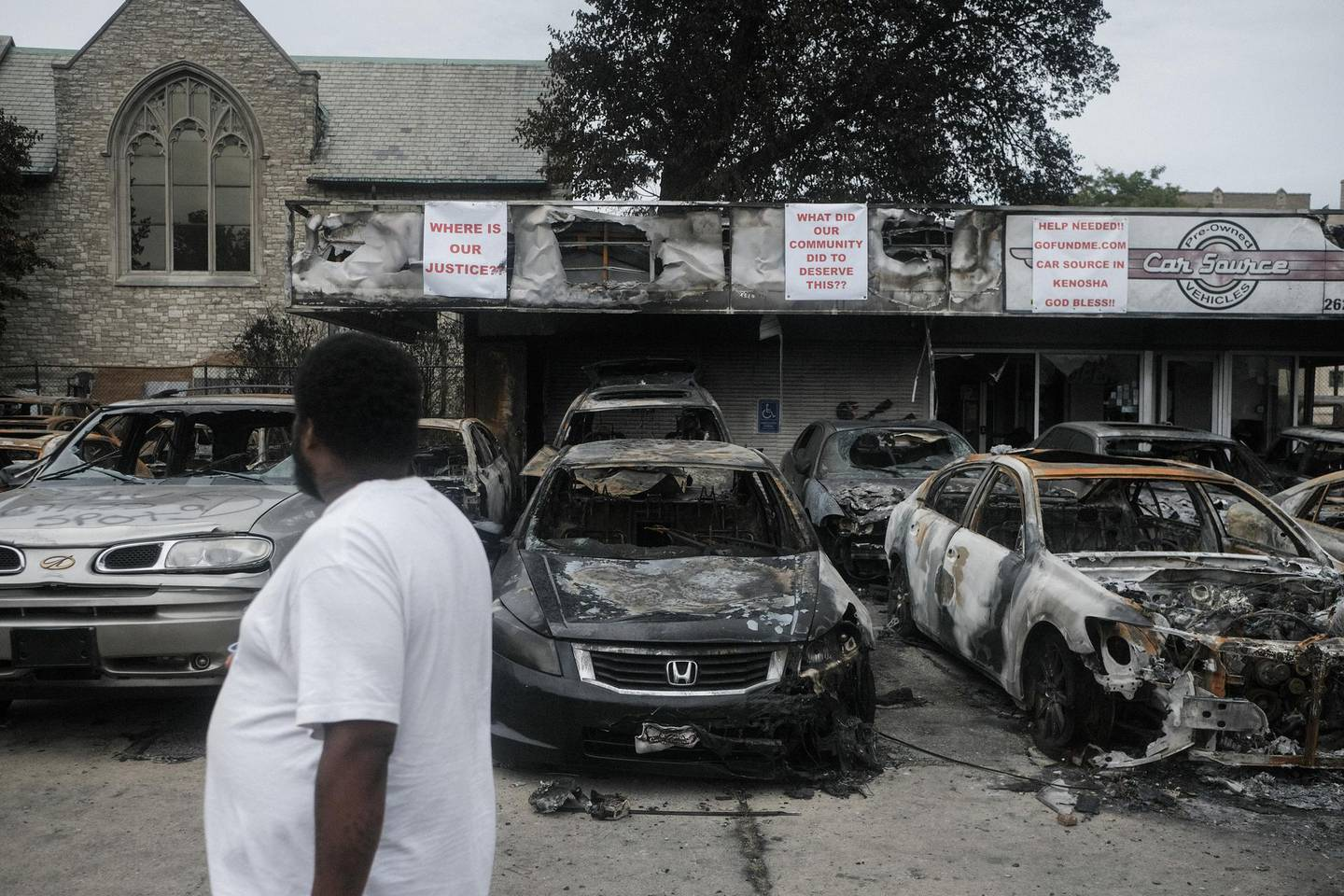 A resident inspects burned out cars at a used car dealership in Kenosha, Wisconsin, U.S., on Tuesday, Sept. 1, 2020. Donald Trump lauded police and National Guard members in Kenosha, Wisconsin, on Tuesday, where the shooting of a Black man by police last month has reignited national protests against racial inequality and street violence the president has sought to blame on Democrats. Photographer: Matthew Hatcher/Bloomberg