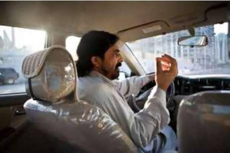 Abu Dhabi - October 6, 2008:  Taxi driver Rab Nawaz Nawaz Mir, from Pakistan speaks arabic, urdu, farsi, dari, and pashtu, drives his cab in Abu Dhabi. ( Philip Cheung / The National ) *** Local Caption ***  PC0048-language2.jpg
