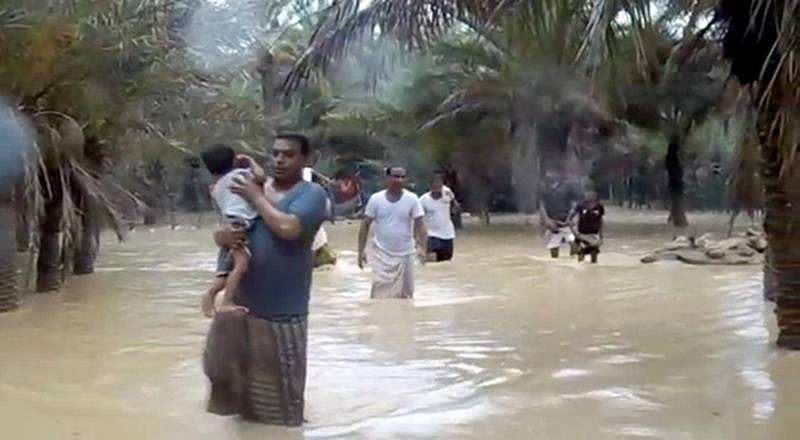 An image grab taken from an AFPTV video shows people walking through flood water as they evacuate a flooded area during a cyclone in the Yemeni island of Socotra. - Seven people were missing and hundreds others evacuated from their homes after a cyclone hit the Yemeni island the previous night, causing severe flooding and damage to houses, officials said. (Photo by STRINGER / AFPTV / AFP)