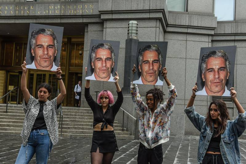 """(FILES) In this file photo taken on July 8, 2019, a protest group called """"Hot Mess"""" hold up photos of Jeffrey Epstein in front of the Federal courthouse on July 8, 2019 in New York City.  The wealthy US financier Jeffrey Epstein, indicted on charges he trafficked underage girls for sex, committed suicide in prison, US news media reported on August 10, 2019. Epstein, who had hobnobbed with politicians and celebrities over the years and was already a convicted sex offender, hanged himself in his cell at the Metropolitan Correctional Center and his body was found around 7:30 Saturday morning, The New York Times and other media said, quoting officials.  / AFP / GETTY IMAGES NORTH AMERICA / STEPHANIE KEITH"""