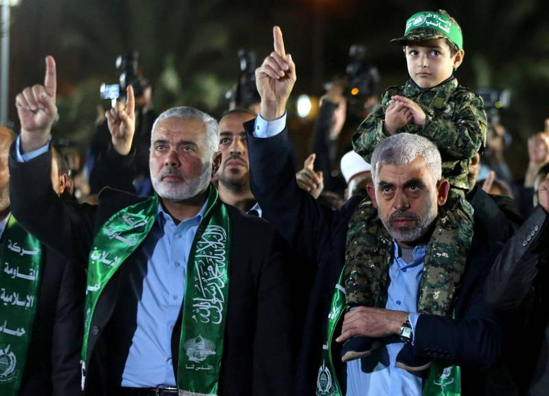 FILE PHOTO: The son of senior Hamas militant Mazen Fuqaha sits on the shoulders of Hamas Gaza Chief Yahya Al-Sinwar as Hamas leader Ismail Haniyeh (L) gestures during a memorial service for Fuqaha, in Gaza City March 27, 2017. REUTERS/Mohammed Salem/File Photo