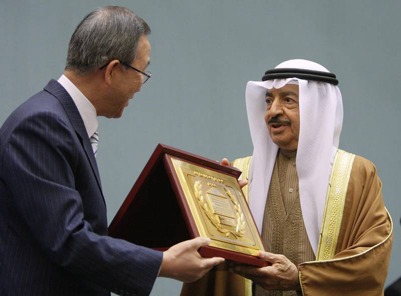 United Nations (UN) Secretary-General Ban Ki-moon (L) gives to Bahraini Prime Minister Sheikh Khalifa bin Salman al-Khalifa  the 2006 Special Citation and Habitat Scroll of Honor on the sideline of the first annual ministerial review of the Economic and Social Council (ECOSOC), 02 July 2007 at the United Nations office in Geneva. The prime minister was awarded by UN-HABITAT, a specialized United Nations agency mandated to promote socially and environmentally sustainable towns and cities.  AFP PHOTO / FABRICE COFFRINI (Photo by FABRICE COFFRINI / AFP)