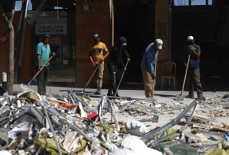 People clean debris from the street following Tuesday's blast in Beirut's port area, Lebanon August 9, 2020. REUTERS/Hannah McKay