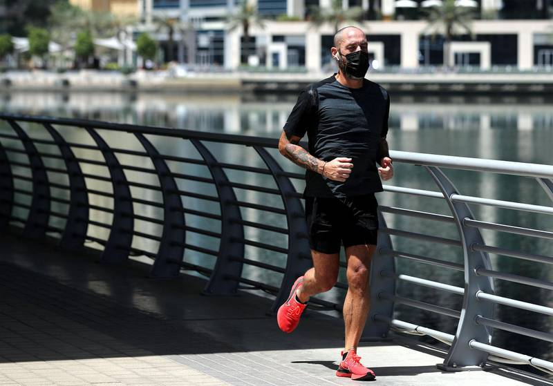 Dubai, United Arab Emirates - Reporter: N/A: Coronavirus. A man exercises in the marina on the first morning where the government has eased restrictions on personal travel due to Covid-19. Friday, April 24th, 2020. Dubai. Chris Whiteoak / The National