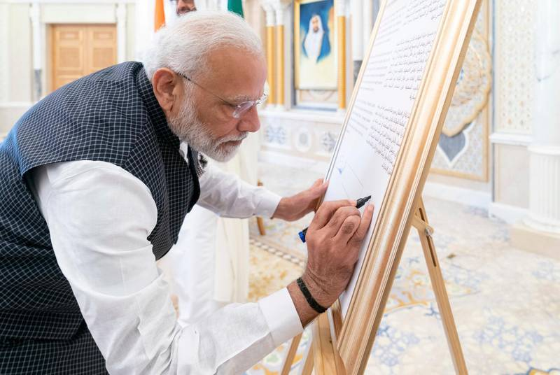 ABU DHABI, UNITED ARAB EMIRATES - August 24, 2019: HE Narendra Modi, Prime Minister of India, signs a board announcing the introduction of a postage stamp celebrating 150 years since the birth of Mahatma Gandhi, during a reception at Qasr Al Watan.  ( Rashed Al Mansoori / Ministry of Presidential Affairs ) ---