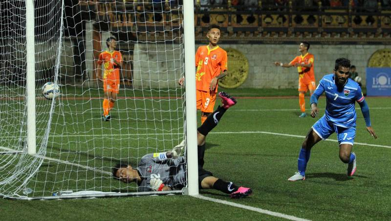 Ali Ashfaq from the Maldives (R) scores the team's second goal against Bhutan's goalkeeper H. Gurung (C) during the FIFA 2018 Asian Group C qualifying football match between Bhutan and Maldives at The Changlimithang Stadium in Thimphu on October 8, 2015. AFP PHOTO / Upasana DAHAL (Photo by UPASANA DAHAL / AFP)