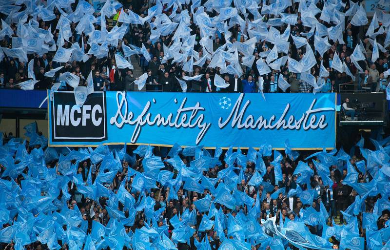 MANCHESTER, ENGLAND - APRIL 17: Manchester City fans wave flags and a banner saying Definitely Manchester in similar style to the Oasis album Definitely Maybe before the UEFA Champions League Quarter Final second leg match between Manchester City and Tottenham Hotspur at at Etihad Stadium on April 17, 2019 in Manchester, England. (Photo by Visionhaus/Getty Images)