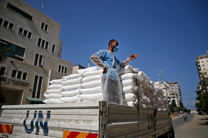 A worker of the United Nations Relief and Works Agency for Palestine Refugees (UNRWA), clad in mask and protective gear due to the COVID-19 coronavirus pandemic, stands in the back of a truck delivering food aid to families in need in Gaza City on September 15, 2020. (Photo by Mohammed ABED / AFP)