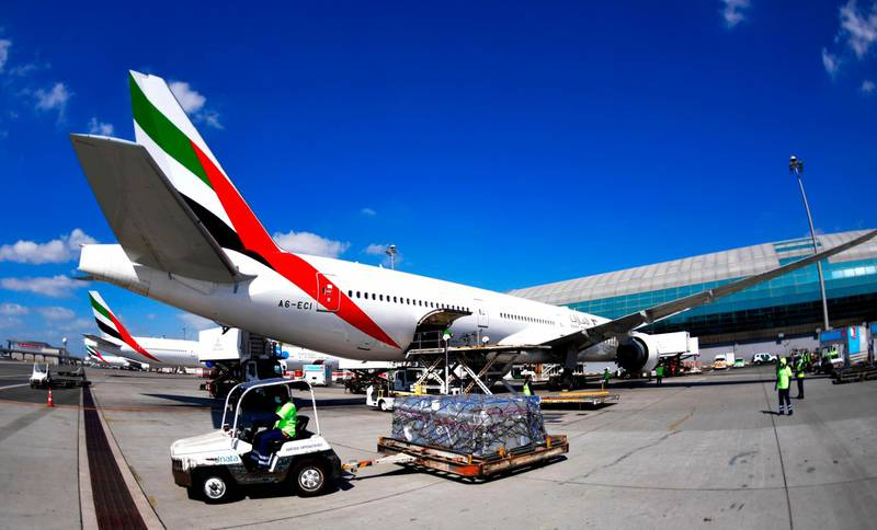 """An Emirates Airlines Boing 777 plane unload a coronavirus vaccine shipment at Dubai International Airport on February 1, 2021 as key transport hub Dubai announced an initiative to accelerate the delivery of coronavirus vaccines, particularly to developing nations. The Vaccine Logistics Alliance, which includes Dubai-based Emirates airline and global logistics giant DP World, is designed to """"speed up distribution of Covid-19 vaccines around the world through the emirate"""". The alliance will """"support"""" the World Health Organization's Covax initiative to distribute two billion vaccine doses, the Dubai Media Office said in a statement, without specifying how many doses it would deliver.  / AFP / Karim SAHIB"""