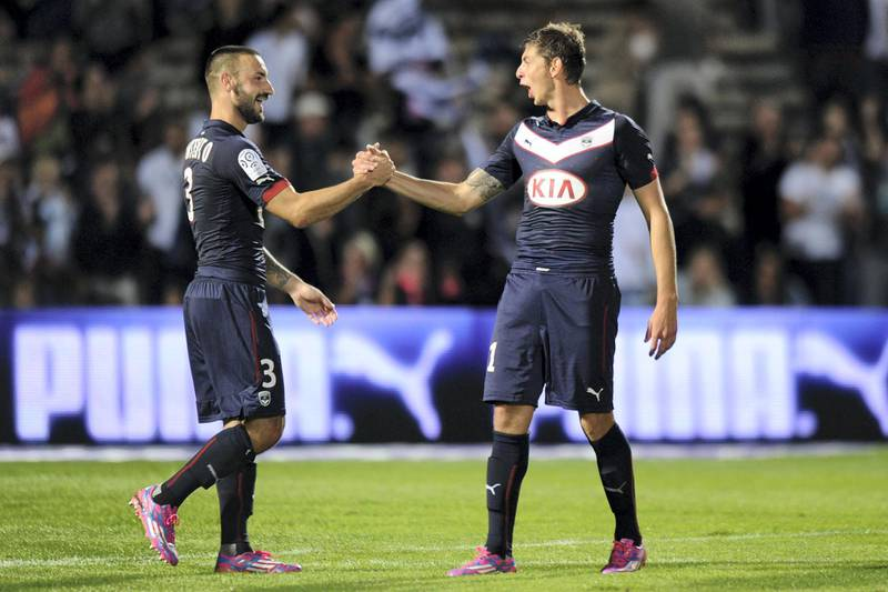 Bordeaux's Diego Contento (L) and Emiliano Sala (R) celebrate at the end of the French L1 football match Bordeaux (FCGB) vs Moncao (ASMFC) on August 17, 2014 at the Chaban Delmas Stadium in Bordeaux. Bordeaux won 4-1. AFP PHOTO / NICOLAS TUCAT (Photo by NICOLAS TUCAT / AFP)