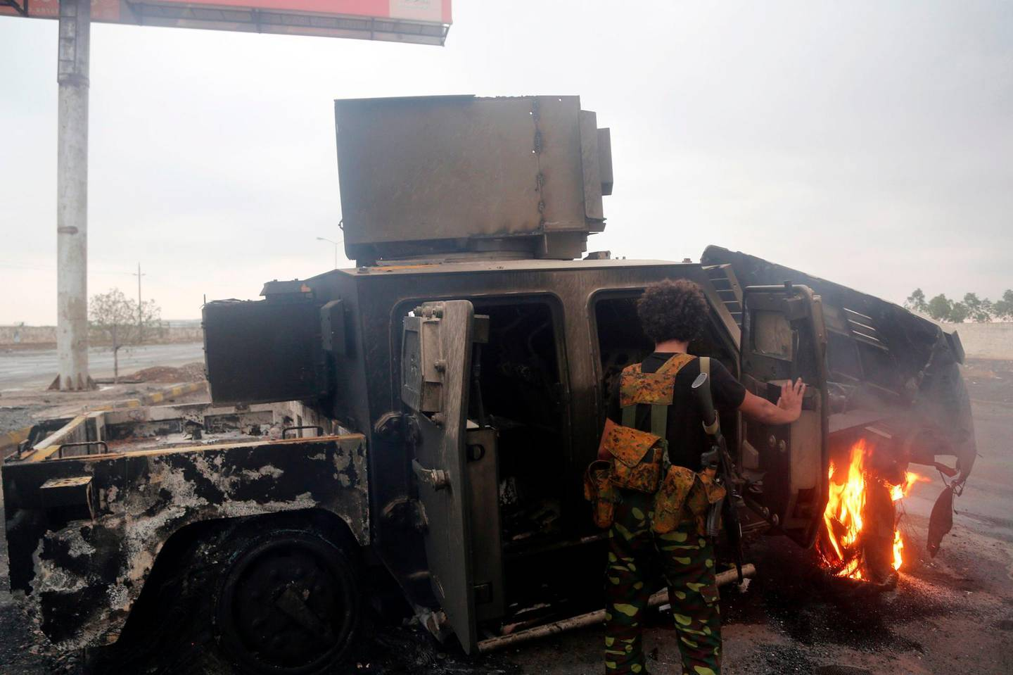 A Huthi rebel inspects a burnt armoured vehicle on September 13, 2018, reportedly destroyed in an air strike during clashes between fighters loyal to Saudi-backed exiled President Abd Rabbo Mansour Hadi and Huthi rebels near the eastern entrance of the Yemeni city of Hodeida, as coalition forces seized rebel supply routes into the coastal city.  Fighting has raged in the last two days close to the rebel-held port city of Hodeida, a crucial entry point for humanitarian aid that the Saudi-led coalition alleges also serves as a key conduit for arms to the Iran-backed Huthis.  / AFP / STRINGER