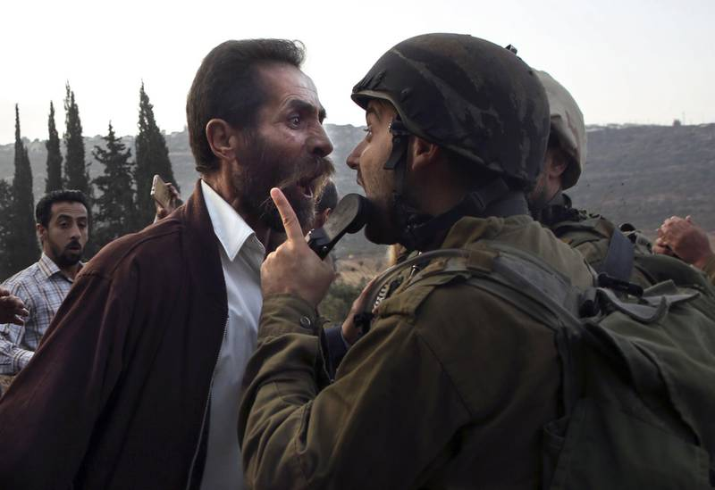 -- AFP PICTURES OF THE YEAR 2018 --  A Palestinian man argues with an Israeli soldier during clashes over an Israeli order to shut down a Palestinian school in the town of as-Sawiyah, south of Nablus in the occupied West Bank on October 15, 2018.  / AFP / JAAFAR ASHTIYEH