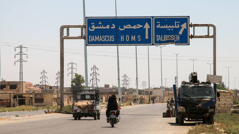 """A picture taken on August 3, 2017 shows vehicles driving past a roadsign that says """"Talbiseh"""" in the eponymous central Syrian rebel-held town, north of Homs, along the highway between the capital Damascus and the central city of Homs. A ceasefire between government forces and rebels went into effect in part of central Syria on August 3, 2017 after Russia struck a deal with the opposition on a safe zone in the northern parts of Homs province.  The truce is the third to be established in Syria, which has been ravaged by six years of civil war that have left more than 300,000 people dead. / AFP PHOTO / MAHMOUD TAHA"""