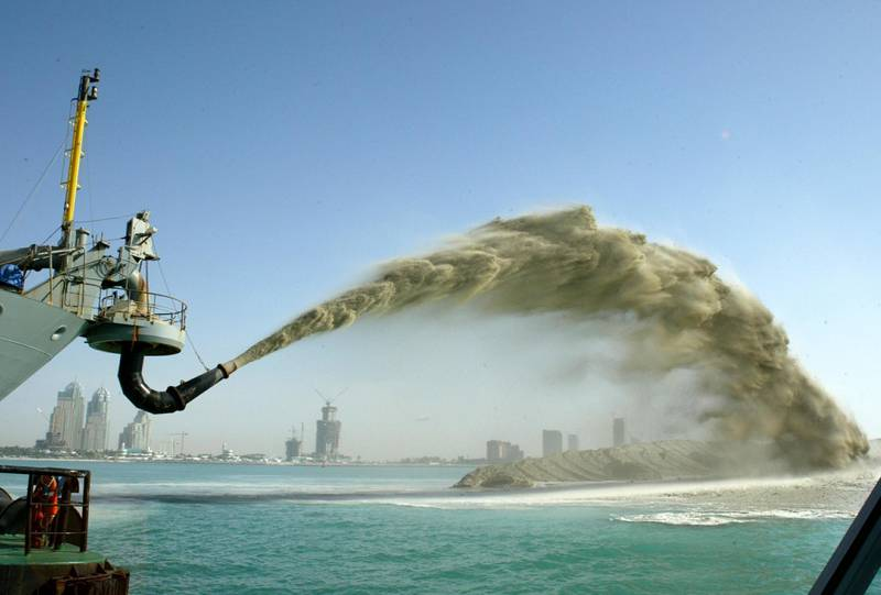 Sand is pumped onto a man-made island part of a $1 billion project in the shape of palm trees off the Dubai coast September 9, 2005. [Thousands of workers from the Indian subcontinent, lured by promises of jobs in the oil-rich United Arab Emirates, toil in scorching heat and high humidity for most of the year. The emirate is fast becoming an architect's playground as more and more outlandish structures take it closer to its dream of being the world's most visually striking metropolis. The infrastructure boom is part of the emirate's ambition to attract foreign cash and investment into an economy that is weaning itself off rapidly-dwindling crude oil reserves.]