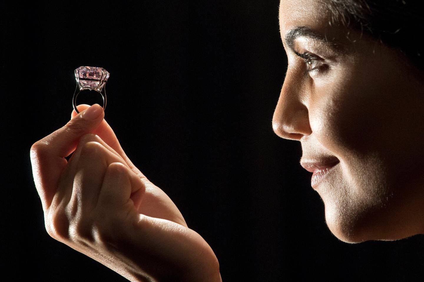 """A model poses with a 59.60-carat oval mixed-cut pink diamond, known as """"The Pink Star"""", during a photocall at Sotheby's auction house in London on March 20, 2017, to promote its forthcoming auction. - The diamond, with an estimated value of 48.5 million GBP (60 million euros; 60 million USD), is said to be the largest Internally Flawless Fancy Vivid Pink diamond that the Gemological Institute of America (GIA) has ever graded, and is set to be auctioned in Hong Kong on April 4, 2017. (Photo by Justin TALLIS / AFP)"""