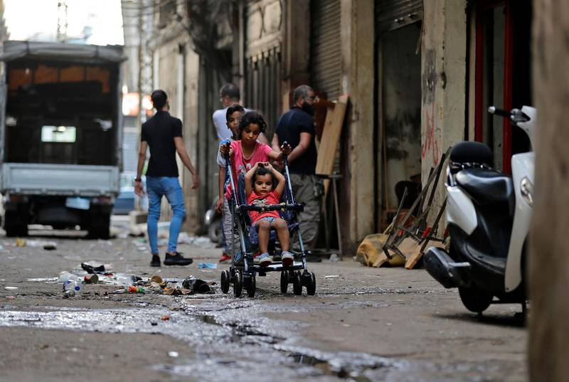 A girl pushes a child stroller with another girl seated, along an alley in the Bab al-Tabbaneh neighbourhood of Lebanon's northern city of Tripoli on June 3, 2020. Thousands of residents of Lebanon's northern Tripoli struggle to put food on the table, as the country's worst economic crisis in decades has picked up in speed in recent weeks, with food prices rising by more than 70 percent since the autumn. Inflation has been a blow in the country where more than 45 percent of the country's population now lives below the poverty line, and more than 35 percent of the workforce is unemployed. / AFP / JOSEPH EID